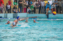 Lviv, Ukraine - July 2015: Ukrainian Cup water polo. Athlete team's water polo ball in a swimming pool and makes attacking shot on Stock Images