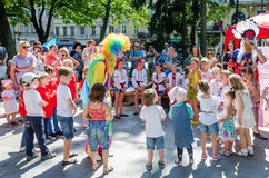 Lviv, Ukraine - July 2015: Yarych street Fest 2015. Clown and Indian play, sing and dance with the children in the park Royalty Free Stock Photos