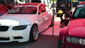 On site there are three cars for racing drift white, blue and red, with stickers. LVIV, UKRAINE - JUN 01, 2019: on site there are three cars for racing drift stock footage