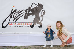 Lviv, Ukraine - June 2015: Alfa Jazz Fest 2015. Little baby girl with her mother sitting next to posters logo Stock Photo