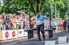 LVIV, UKRAINE - JUNE 2016: Athlete bodybuilder strongman with strong body has an enormous metal structure with pancakes with rod o Royalty Free Stock Image