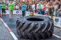 LVIV, UKRAINE - JUNE 2016: Athlete bodybuilder strongman with strong body pushes a huge turning the wheel of a truck tire Stock Photo