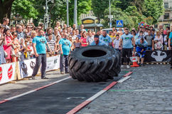 LVIV, UKRAINE - JUNE 2016: Athlete bodybuilder strongman with strong body pushes a huge turning the wheel of a truck tire Royalty Free Stock Images