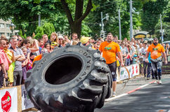 LVIV, UKRAINE - JUNE 2016: Athlete bodybuilder strongman with strong body pushes a huge turning the wheel of a truck tire Stock Image