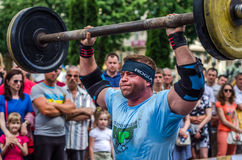 LVIV, UKRAINE - JUNE 2016: Athlete strongman inflated with athletic body lifting heavy barbell on a city street royalty free stock photography