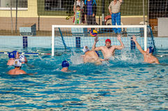 LVIV, UKRAINE - JUNE 2016: Athletes water polo players fighting for the ball with the opponents in the pool of water in a spray Royalty Free Stock Photo