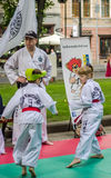 LVIV, UKRAINE - JUNE 2016: Children boy and girl in a kimono show their skills during a training for taekwondo bout in front of hi. Children boy and girl in a Royalty Free Stock Photo