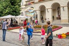 Lviv, Ukraine - June 2015: Guy entertains children at the center of Lviv, at Market Square for children starting huge soap bubbles Stock Photo