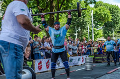 LVIV, UKRAINE - JUNE 2016: Strong athlete bodybuilder strongman lifts a heavy barbell in front of the audience on a city street Stock Image