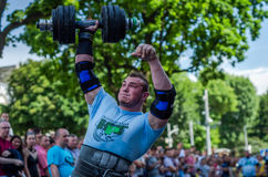 LVIV, UKRAINE - JUNE 2016: Strong athlete bodybuilder strongman lifts heavy dumbbell in front of the audience on a city street Royalty Free Stock Images
