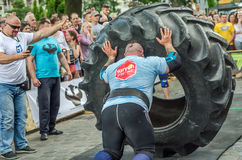 LVIV, UKRAINE - JUNE 2016: Strong bodybuilder athlete, the athlete rolls the wheel of a huge black Goodyear from the truck on the Royalty Free Stock Images