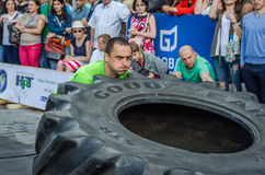 LVIV, UKRAINE - JUNE 2016: Strong bodybuilder athlete, the athlete rolls the wheel of a huge black Goodyear from the truck on the Stock Image