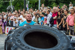 LVIV, UKRAINE - JUNE 2016: Strong bodybuilder athlete, the athlete rolls the wheel of a huge black Goodyear from the truck on the Stock Photo