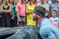 LVIV, UKRAINE - JUNE 2016: Strong bodybuilder athlete, the athlete rolls the wheel of a huge black Goodyear from the truck on the Stock Images