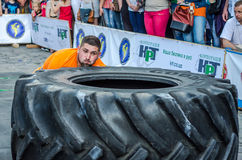 LVIV, UKRAINE - JUNE 2016: Strong bodybuilder athlete, the athlete rolls the wheel of a huge black Goodyear from the truck on the Royalty Free Stock Photography