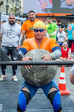 LVIV, UKRAINE - JUNE 2016: Strong bodybuilder strongman lifts a huge heavy stone ball made of marble and throws it over the bar on Stock Photography