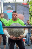 LVIV, UKRAINE - JUNE 2016: Strong bodybuilder strongman lifts a huge heavy stone ball made of marble and throws it over the bar on Royalty Free Stock Images