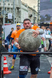 LVIV, UKRAINE - JUNE 2016: Strong bodybuilder strongman lifts a huge heavy stone ball made of marble and throws it over the bar on Stock Images
