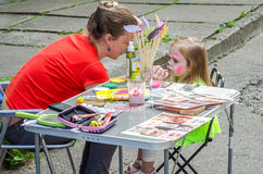LVIV, UKRAINE - JUNE 2016: Woman master artist paints a sweet charming girl child on the face of mustache and a cat mask on a chil Royalty Free Stock Photography
