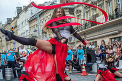 LVIV, UKRAINE - JUNE 2016: Young charming sexy girls perform a dance with her on the street in front of the audience in the red, w Stock Photos