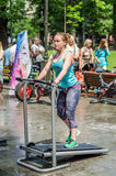 LVIV, UKRAINE - JUNE 2016: Young charming sports girl in the street shows different exercises on fitness Royalty Free Stock Photos