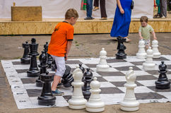 LVIV, UKRAINE - JUNE 2016: Young children, the future grandmasters play on a chess board chess exercising outdoors huge figures Royalty Free Stock Images