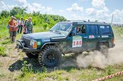 LVIV, UKRAINE - MAI 2016 : Jeep accordée énorme SUV de voiture conduisant sur un rassemblement de chemin de terre, soulevant un n Photographie stock
