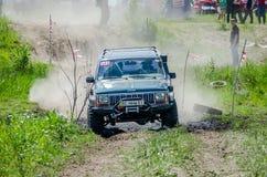 LVIV, UKRAINE - MAI 2016 : Jeep accordée énorme SUV de voiture conduisant sur un rassemblement de chemin de terre, soulevant un n Images libres de droits