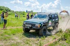 LVIV, UKRAINE - MAI 2016 : Jeep accordée énorme SUV de voiture conduisant sur un rassemblement de chemin de terre, soulevant un n Images stock