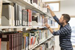 Lviv, Ukraine - March 28, 2019: Student look for a book in Ukrainian Catholic University library. Education theme. Lviv, Ukraine - March 28, 2019: Student look stock photography