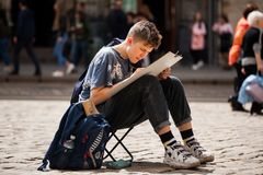LVIV UKRAINE - May 17, 2019: Boy create outdoors sketches. Learner paint the urban landscape of the old European city royalty free stock images
