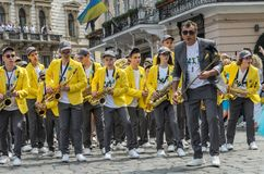 LVIV, UKRAINE - MAY 2018: A brass band with trumpets and saxophones in carnival costumes with yellow jackets is walking along the. A brass band with trumpets and royalty free stock image