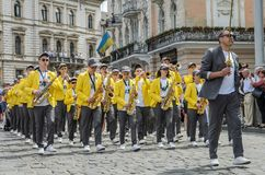 LVIV, UKRAINE - MAY 2018: A brass band with trumpets and saxophones in carnival costumes with yellow jackets is walking along the. A brass band with trumpets and stock photo
