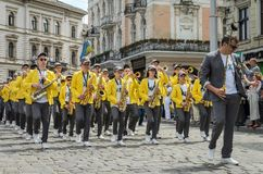 LVIV, UKRAINE - MAY 2018: A brass band with trumpets and saxophones in carnival costumes with yellow jackets is walking along the. A brass band with trumpets and royalty free stock images