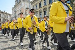 LVIV, UKRAINE - MAY 2018: A brass band with trumpets and saxophones in carnival costumes with yellow jackets is walking along the. A brass band with trumpets and stock photos
