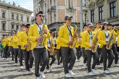 LVIV, UKRAINE - MAY 2018: A brass band with trumpets and saxophones in carnival costumes with yellow jackets is walking along the. A brass band with trumpets and stock images