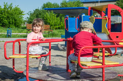 LVIV, UKRAINE - MAY 2017: Children boy and girl ride on a swing on a bright sunny day Stock Images