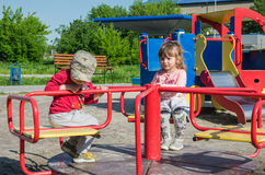 LVIV, UKRAINE - MAY 2017: Children boy and girl ride on a swing on a bright sunny day Royalty Free Stock Photo
