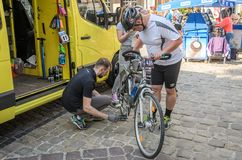 LVIV, UKRAINE - MAY 2018: The cyclist repairs his bicycle by pumping a punctured wheel. The cyclist repairs his bicycle by pumping a punctured wheel stock photography