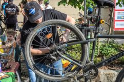 LVIV, UKRAINE - MAY 2018: The cyclist repairs his bicycle by pumping a punctured wheel. The cyclist repairs his bicycle by pumping a punctured wheel stock image