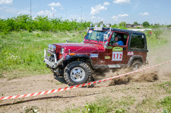LVIV, UKRAINE - MAY 2016: Huge tuned car Jeep SUV driving on a dirt road rally, raising a cloud of dust behind, among the spectato Royalty Free Stock Photo