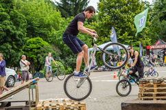 LVIV, UKRAINE - MAY 2016: The sportsman on a bicycle helmet is racing at high speed bouncing jumping competition during downhill stock photo