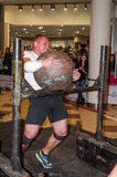 LVIV, UKRAINE - NOVEMBER 2016: Strong athlete strongman carries heavy iron suitcases Royalty Free Stock Image