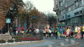 Group of athletes, healthy people running down street, taking part in marathon. LVIV, UKRAINE - OCT 13, 2019: A group of athletes, healthy people running down stock video footage