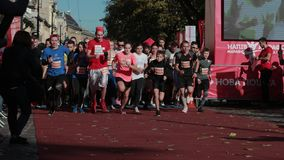 Large number of people start at the start, take part in a running marathon. LVIV, UKRAINE - OCT 13, 2019: a large number of people start at the start, take part stock footage