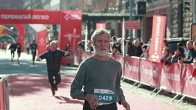 Grandfather of athletic build with a gray beard finishes in a running marathon. LVIV, UKRAINE - OCT 13, 2019: An old grandfather of athletic build with a gray stock video footage