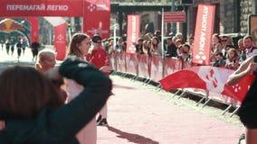 A young athlete runs through the finish line finishing in running marathon. LVIV, UKRAINE - OCT 13, 2019: A young athlete runs through the finish line finishing stock footage