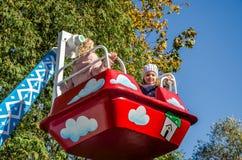 LVIV, UKRAINE - OCTOBER 2017: Little children, charming girls girlfriends ride in an amusement park on a swing Royalty Free Stock Photos