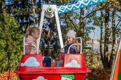 LVIV, UKRAINE - OCTOBER 2017: Little children, charming girls girlfriends ride in an amusement park on a swing Stock Photo