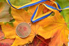 Lviv/Ukraine - October 7 2018: Medal from autumn Kid`s bicycle race in Lviv. Yellow maple leaves us a background. Medal for participation stock image